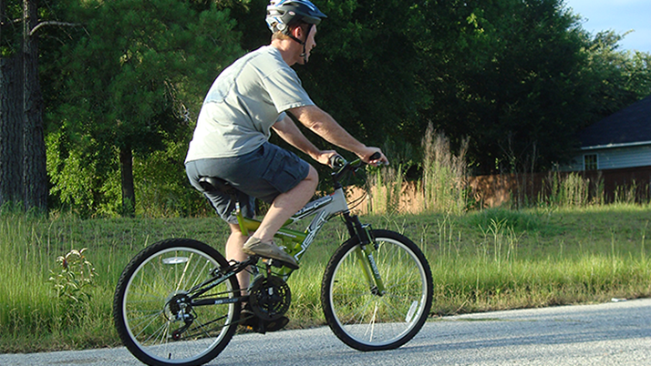 man with helmet riding a bicycle on the road